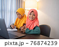 smiling young muslim kid with laptop together 76874239