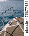 Close up view of the bow of a white yacht sailing on the blue sea 76877484