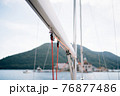 Winch of white sailing yacht with a red rope on a background of mountains 76877486