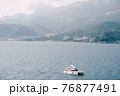 White sailing yacht floats on the sea against the background of the city in the mountains 76877491