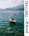 Small boat is anchored near the shore on a sunny day. Against the backdrop of mountains and sea 76877492