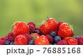 Pile od strawberries, blueberries, raspberries on green background 76885168