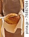 Baker holding loaf of homemade bread 76887684