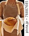 Baker holding loaf of homemade bread 76887685