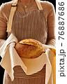 Baker holding loaf of homemade bread 76887686