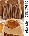 Baker holding loaf of homemade bread 76887690