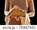 Baker holding loaf of homemade bread 76887691