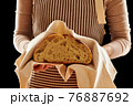 Baker holding loaf of homemade bread 76887692