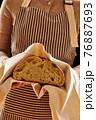 Baker holding loaf of homemade bread 76887693