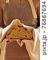 Baker holding loaf of homemade bread 76887694