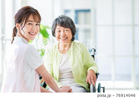 介護する若い女性と車いすの高齢者 76914046