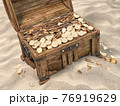 Open treasure chest full of golden coins on sandy beach. Wealth and treasure concept. 76919629