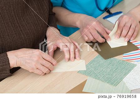 介護イメージ 折り紙で遊ぶヘルパーと高齢者 76919658