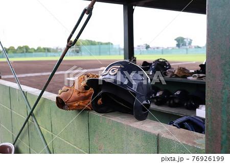 高校野球のベンチ内に置かれたグローブとヘルメット 76926199