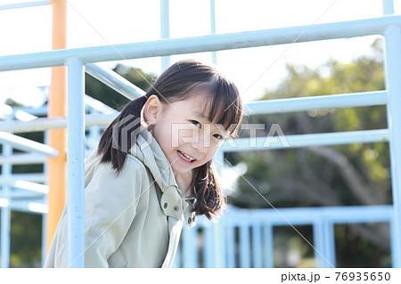 公園のジャングルジムで遊ぶ5歳の女の子 76935650