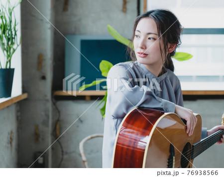 窓際でギターを抱えている若い女性 76938566