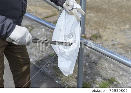 ゴミ拾いをするシニア男性(顔なし) 76939302