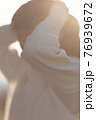 長い髪をまとめる女性 76939672