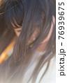 風でなびく髪の隙間から見える微笑み 76939675