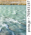 Turquoise waters with white foam and bank with grass of Sochi river.. Mountain river with clear water flows from Caucasus mountains. Sochi, Russia. 76943197