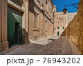 Buildings with old fashioned lanterns and balconies. Ancient narrow street in Mdina, Malta. 76943202