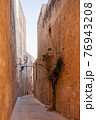 Buildings with old fashioned lanterns and balconies. Ancient narrow street in Mdina, Malta. 76943208
