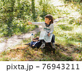 Little explorer on hike in forest. Boy with binoculars and compass sits on stump and reads map. Outdoor leisure activity for children. Summer journey for young tourist. 76943211