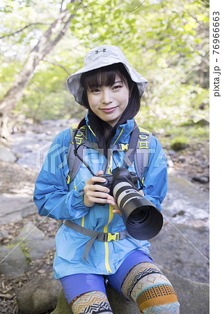 山で一眼レフカメラを持つ若い女性 トレッキングイメージ 76966663