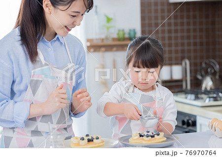 ファミリー ホットケーキ作りを楽しむ女の子 76970764