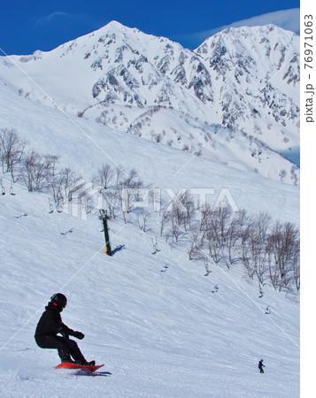 白馬八方尾根スキー場 白馬三山を背景に黒菱ゲレンデを滑るスノーボーダー 76971063
