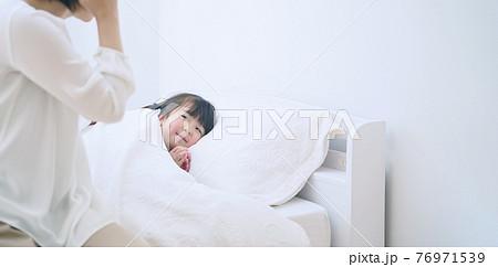 女の子を寝かしつける女性 子育て・保育イメージ 76971539
