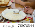 Close-up of a boy's hand with a spoon of porridge over a plate. 76978344