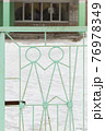 An iron lattice with metal figures of people of light green color. 76978349