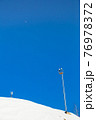 Ski resort, gentle snow slope with artificial lighting towers. 76978372