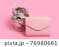 Euro and dollar banknotes in glass money jar with blank label and pink wallet, financial, saving.Moneybox with empty sticky note paper. Jar full of cash, save money concept, expense planning, control 76980661