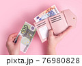 Hands holding wallet, counting cash or paying. Pink leather wallet with euro money in female hands. Woman's hands taking European bank notes out of purse. Money, finances, shopping. Free copy space. 76980828