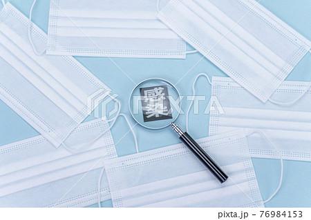 新型コロナイメージ マスクと拡大鏡と感染の文字 76984153