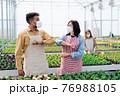 Workers greeting in greenhouse in garden center, coronavirus concept. 76988105