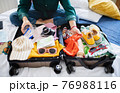 Unrecognizable woman with suitcase packing for holiday at home, coronavirus concept. 76988116