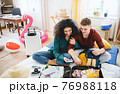 Young couple with laptop packing for summer holiday, coronavirus concept. 76988118