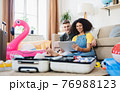 Cheerful young couple packing for summer beach holiday at home, using tablet. 76988123