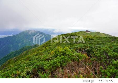 中ノ岳山頂からの避難小屋と八海山 76991451
