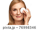 Portrait of a beautiful elderly woman in a white shirt removing makeup with a cleanser and a cotton pad. 76998346