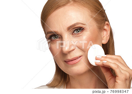 Portrait of a beautiful elderly woman in a white shirt removing makeup with a cleanser and a cotton pad. 76998347