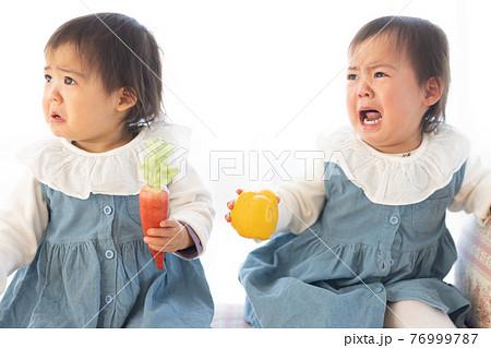 泣いている双子の幼児 76999787