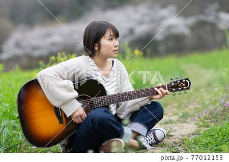 ギターを背負ったミュージシャン 77012153