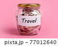 Money box with word TRAVEL on sticky note paper. Dollars in glass jar with savings label, financial, saving. Jar full of american dollar bills, cash, save money concept, expense planning, control. 77012640