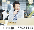 young asian business person sitting at desk thinking hard. 77024413