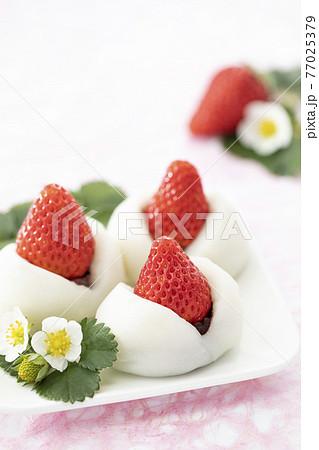 まるごとイチゴを乗せたイチゴ大福と横に添えたイチゴの葉と花 77025379
