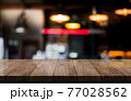 Empty wooden table top with lights bokeh on blur restaurant background 77028562